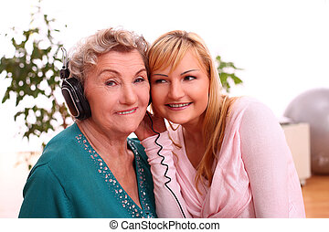 Happy elderly woman with granddaughter listening to the...