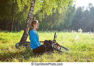 Woman cyclist enjoying relaxation in sunny park