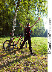 Excited young cyclist standing in a spring park with hands outstretched. Sunny outdoor