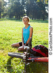 Woman cyclist enjoying relax in spring park