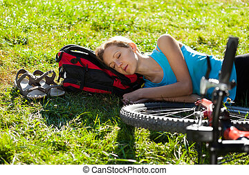Young girl cyclist enjoying sleeps relax lying in the fresh grass on spring sunny meadow. Outdoor
