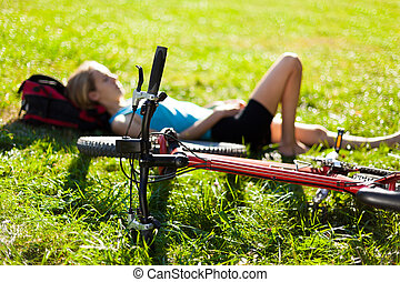 Young girl cyclist enjoying relaxation lying in the fresh green grass illuminated by the rays of sunlight. Outdoor