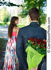 Young man keeps behind his back a bouquet of red roses gift a his girlfriend in a summer park
