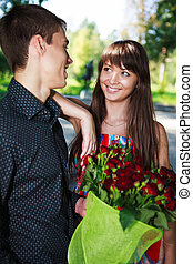 Portrait cheerful young couple with a bouquet of red roses