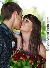 Portrait lovers kissing young couple with a bouquet of red roses. Summer outdoor