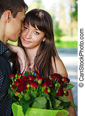 Portrait lovers beautiful young couple with a bouquet of red roses. Summer park
