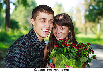 Portrait laughing lovers young couple with a bouquet of red roses. Summer outdoor