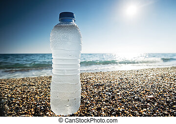 Bottle of fresh water is on sand