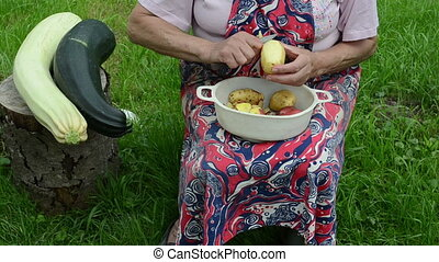 hand peel potato zucchini - old woman with apron hands peel...