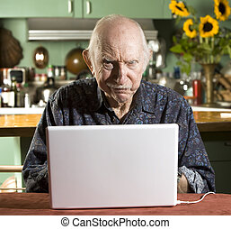 Grumpy Senior Man with a Laptop Computer - Grumpy Senior in...