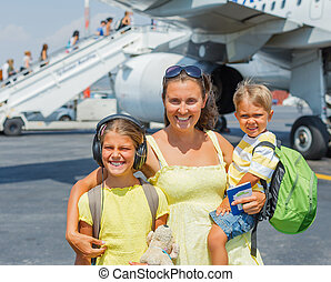 Mother with two kids in front of airplane - Young mother...