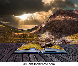 Moody dramatic mountain sunset landscape in pages of book -...