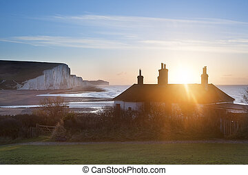 Sun bursts over coastguard cottages at Seaford Head with...