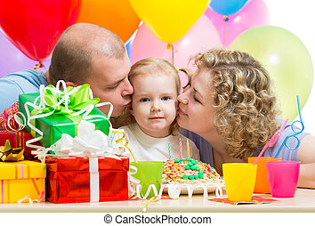 parents kissing kid girl on birthday party