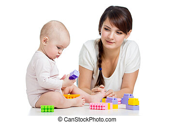 baby girl and mother playing together with construction set toy