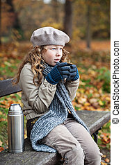 Girl in winter cloths drinking from flask cup - Outdoor...