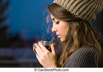 Young brunette with hot tea. - Portrait of a dreamy young...
