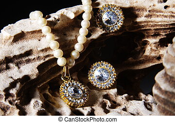 Pearl necklace & earrings on a rock - A pearl necklace...