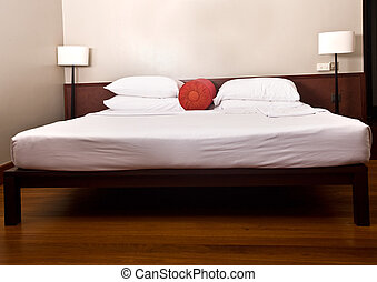 Bed and headboard in bedroom with lamp. Interior.
