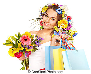 Woman with shopping bag holding flower.
