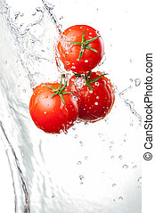 Three Fresh red Tomatoes in splash of water Isolated on...