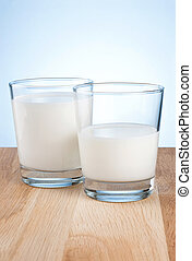Full and half Glass of fresh milk is on wooden table a blue...