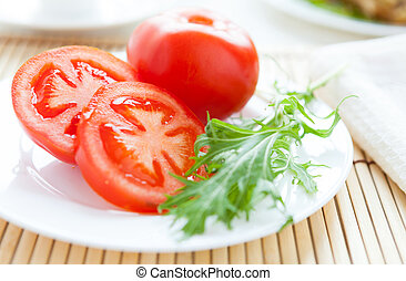 Ripe tomato on a white plate and salad leaves, closeup