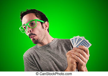 guy spying poker cards on green background