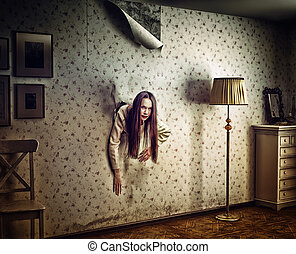 horror - angry woman climbs through the wall into the room...