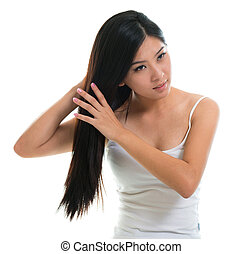 Hair care. Young Asian girl combing hair with finger...