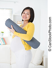 Asian pregnant woman holding yoga mat, having yoga at home