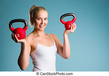 Girl and kettlebell - Fitness girl holds two kettlebells,...
