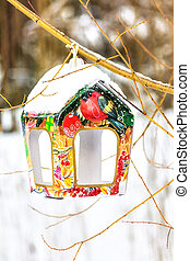 Snow covered colorful birdfeeder on the trunk of tree in a...