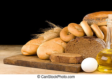 bread and bakery products on wood isolated at black...