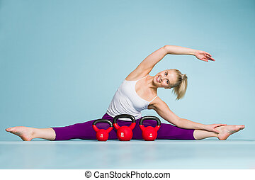 Girl and kettlebell - Fitness girl stretching and the...