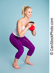 Girl and kettlebell - Fitness girl in half squat position...