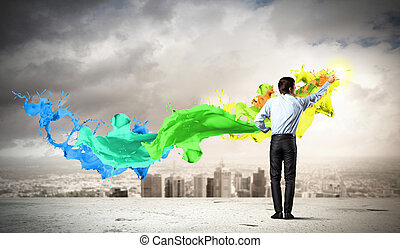 Man painting splashes - young man standing with back...