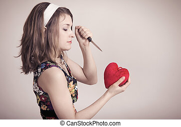 woman cutting a toy heart with a knife