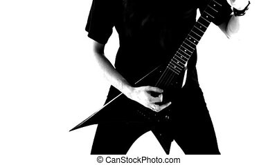 Heavy metal musician playing guitar in a studio. Black and...