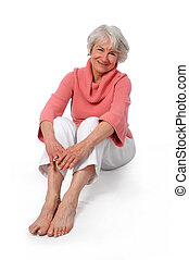 Woman smiling - Attractive senior woman smiling sitting over...
