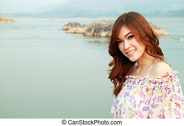 a portrait of beautiful woman with river background