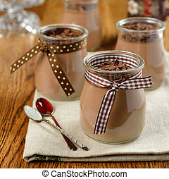 Chocolate dessert in a small glass jar on a brown table