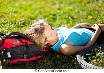 Young girl cyclist enjoying relaxation lying in the fresh grass