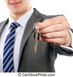 Young realtor handing keys on white background