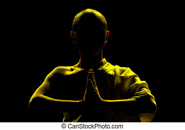 monk praying - silhouette of monk praying in lotus position...