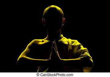 monk praying - silhouette of monk praying in lotus position...
