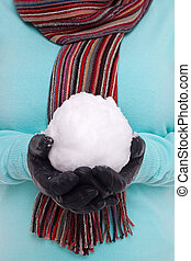 Woman holding a snowball - Woman wearing a knitted scarf and...