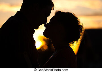 Profiles of romantic couple looking at each other on sunset...