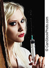 Sexy young girl in the image of nurse with syringe in hand....