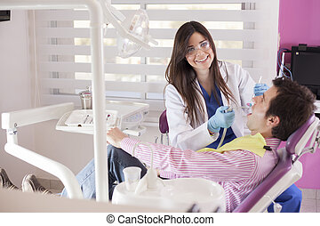 Cute dentist at work - Beautiful female dentist working on a...